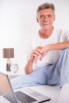 年配の男性は、ベッドに座ってラップトップを使用しています。