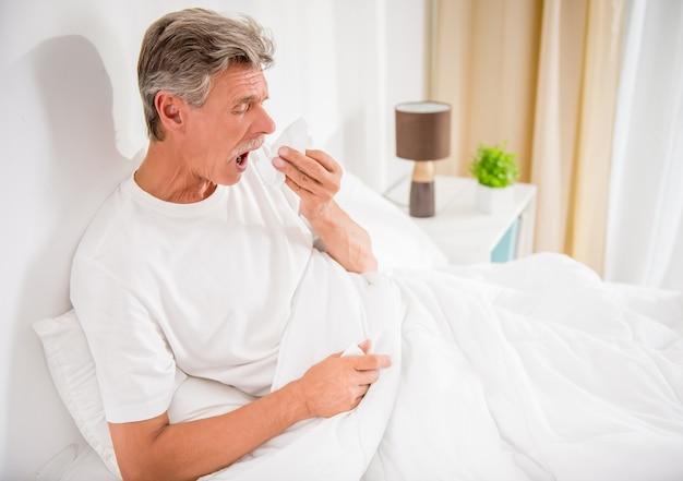 年配の男性が鼻をかむ、彼は風邪をひいています。