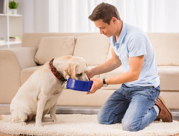若い男は床に座って彼の犬に餌をやります。