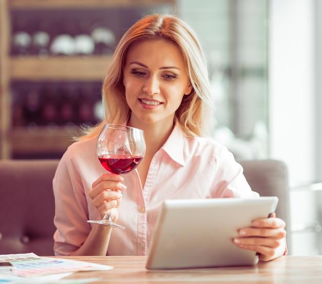 ビジネスの女性は、タブレットを使用してワインを飲みます。