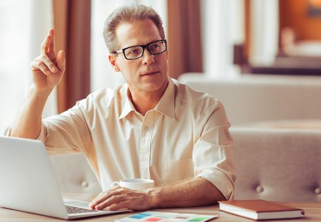 眼鏡のハンサムな実業家は、ラップトップを使用しています。
