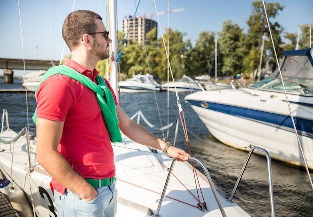 男がボートの上に立って、遠くを見ます。