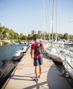 男はボートの間を歩きます。