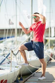 ショートパンツの男が立って、ヨットにつかまります。