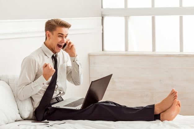 携帯電話とベッドの上に座ってラップトップを使用して男