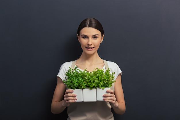 エプロンの美しい少女は植物を保持しています。