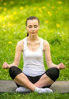 夏の公園のマットの上に座って、ヨガをやっているスポーティな女の子