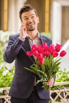 チューリップの花束を押しながら電話で話している男性。