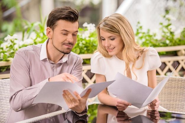 レストランでメニューを読んで美しい若いカップル。
