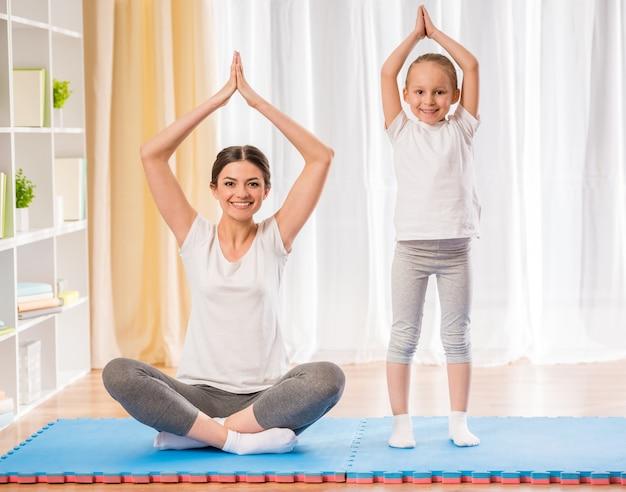 母と娘が自宅の敷物でヨガの練習を行います。