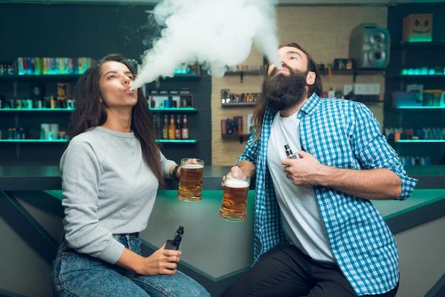 男と女が両手にビールを持って座っています。