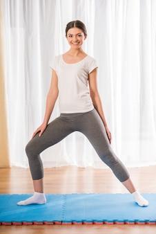 若い女の子は、自宅で運動を行います。