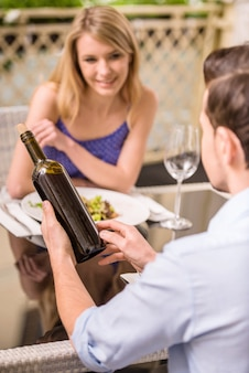 女性は彼氏の向かいのレストランに座っています。