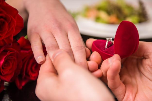 彼のガールフレンドにリングで提案をする男。