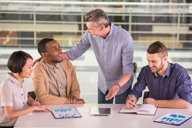 オフィスで会議を行っているビジネス人々のグループ。