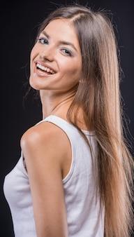顔を作るタンクトップで遊び心のある若い茶色の髪の女性。