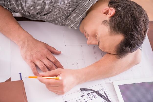 Усталый рабочий человек спит на рабочем месте, полном эскизов.