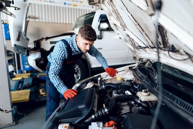 Молодой автомеханик смотрит под капотом.