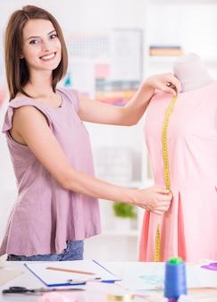 スタジオで測定を行う女性のファッションデザイナー。
