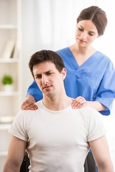 男性患者に首のマッサージを作る女性医師。