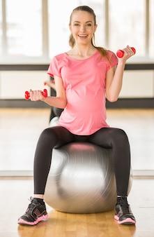 Женщина делает упражнения с помощью фитнес мяч и гантели.