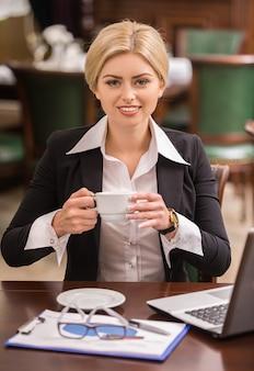 カフェのテーブルに座っている自信を持って女性実業家。