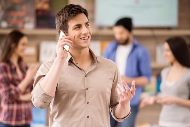 インテリアデザイナーは、オフィスで電話でカジュアルな話を着ています。