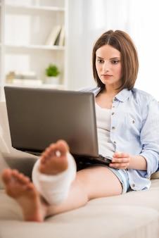 ソファに座って脚に石膏を持つ美しい少女。