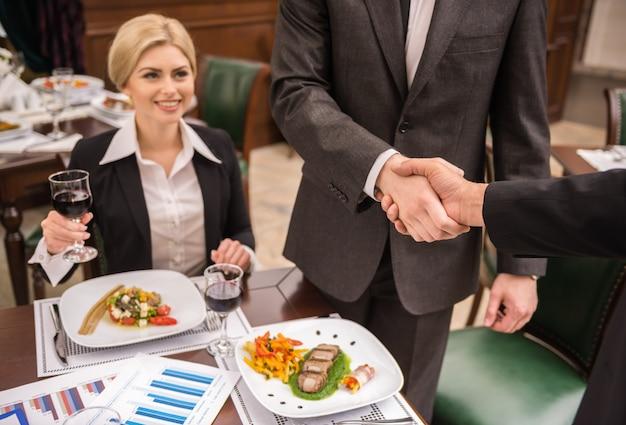 ビジネスランチをとりながら握手するパートナー。