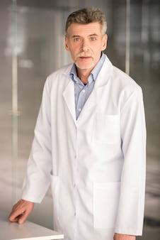 Старший профессор химии, стоя в лаборатории.