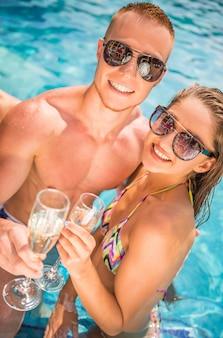 カップルはプールで楽しんでいる間シャンパンを飲んでいます。