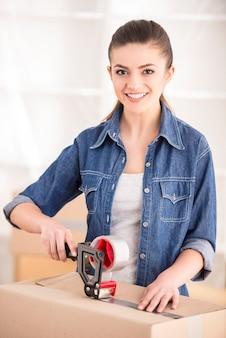 若い幸せな女性の梱包箱。