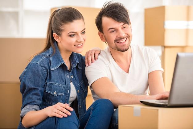 幸せなカップルがノートパソコンでアパートを探しています。