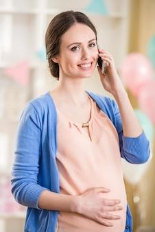 美しい妊娠中の女性は電話で話しています。