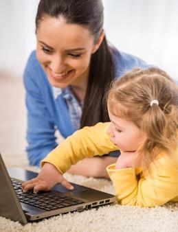 若い母親と彼女の愛らしい娘はラップトップを使用しています。