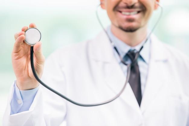 聴診器を押しながら笑みを浮かべて男性医師のクローズアップ。