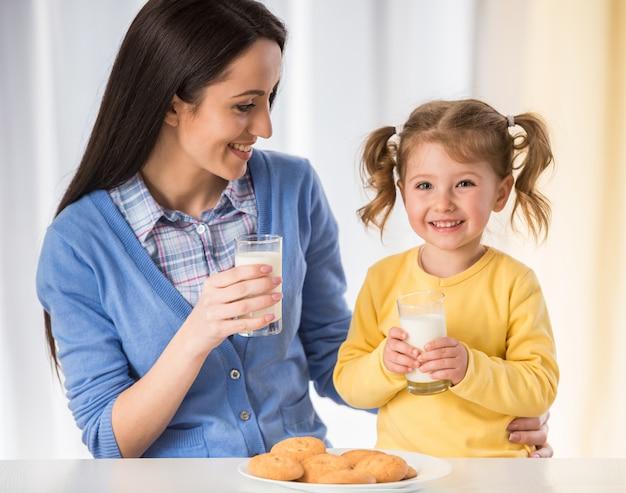 女の子は、クッキーとミルクで健康的なスナックを食べています。