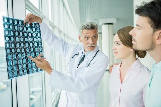 Опытный врач-мужчина показывает пациентам результаты рентгеновских исследований.