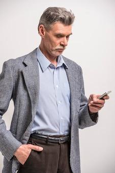 電話を使用して年配の男性の肖像画。
