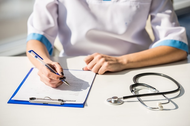 女の子の医者はテーブルに座って書いています。