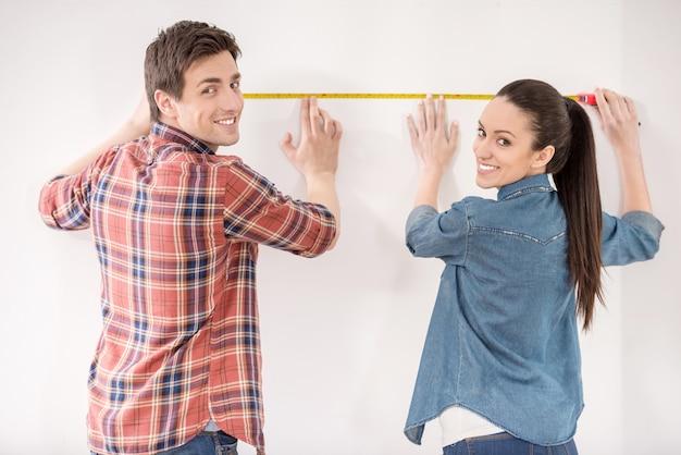 幸せなカップルは、彼らの新しい空のアパートを測定しています。