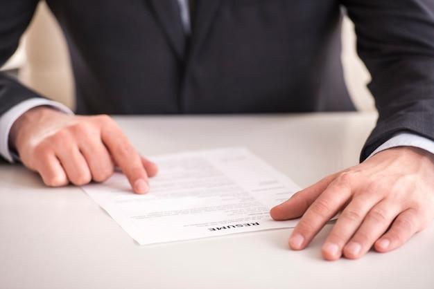 ビジネスマンのオフィスの机で履歴書を分析します。