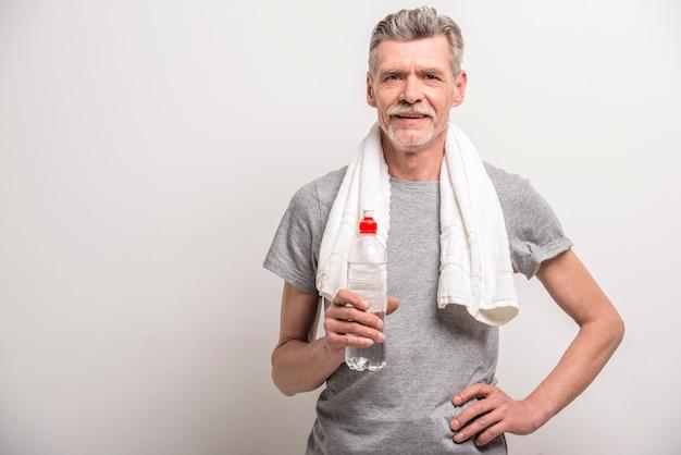 Улыбающийся человек в футболке на шее полотенце с бутылкой воды.