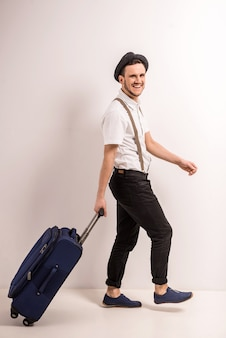 帽子のハンサムな若い男はスーツケースで歩いています。