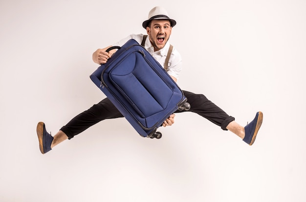 Мужчина позирует с чемоданом