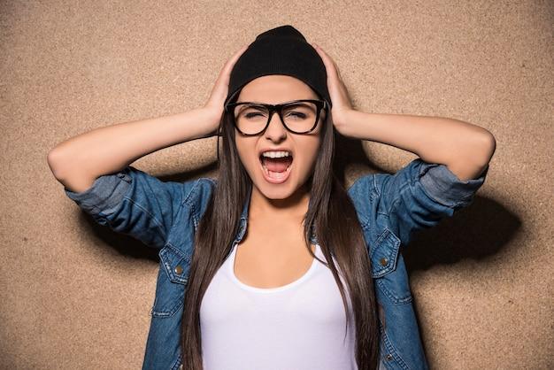 叫んでメガネの若い美しさのブルネットの少女。