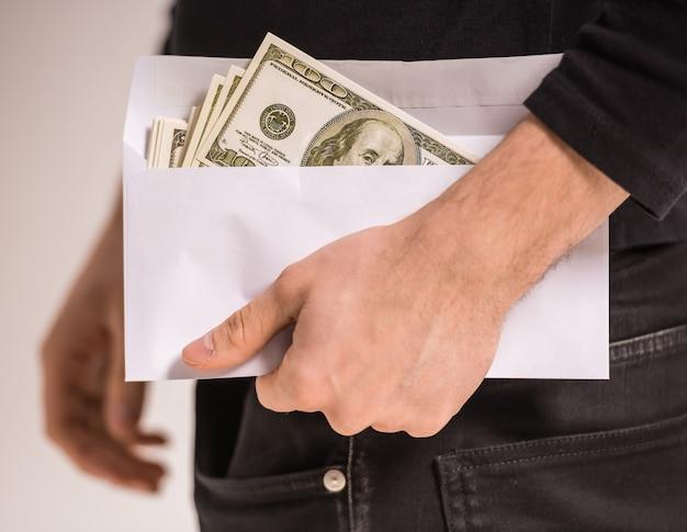 男のクローズアップ手はお金で封筒を保持しています。