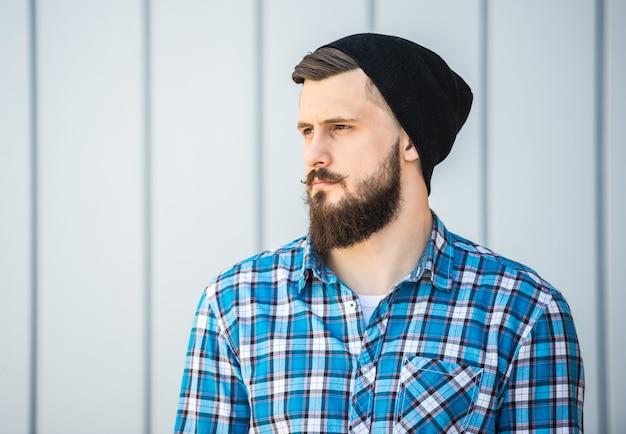 屋外の帽子のひげを生やした男の側面図。