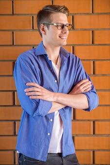 スマートカジュアルな服装でハンサムな若い男の側面図です。
