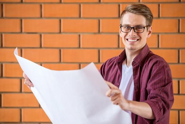 Молодой человек в очках, держа бумаги ватман.
